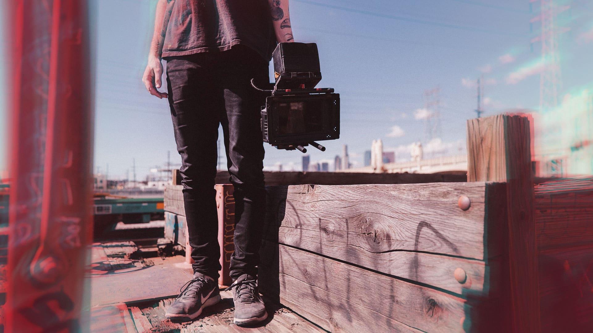 personne sur les toits d'une ville tenant une caméra dans la main droite