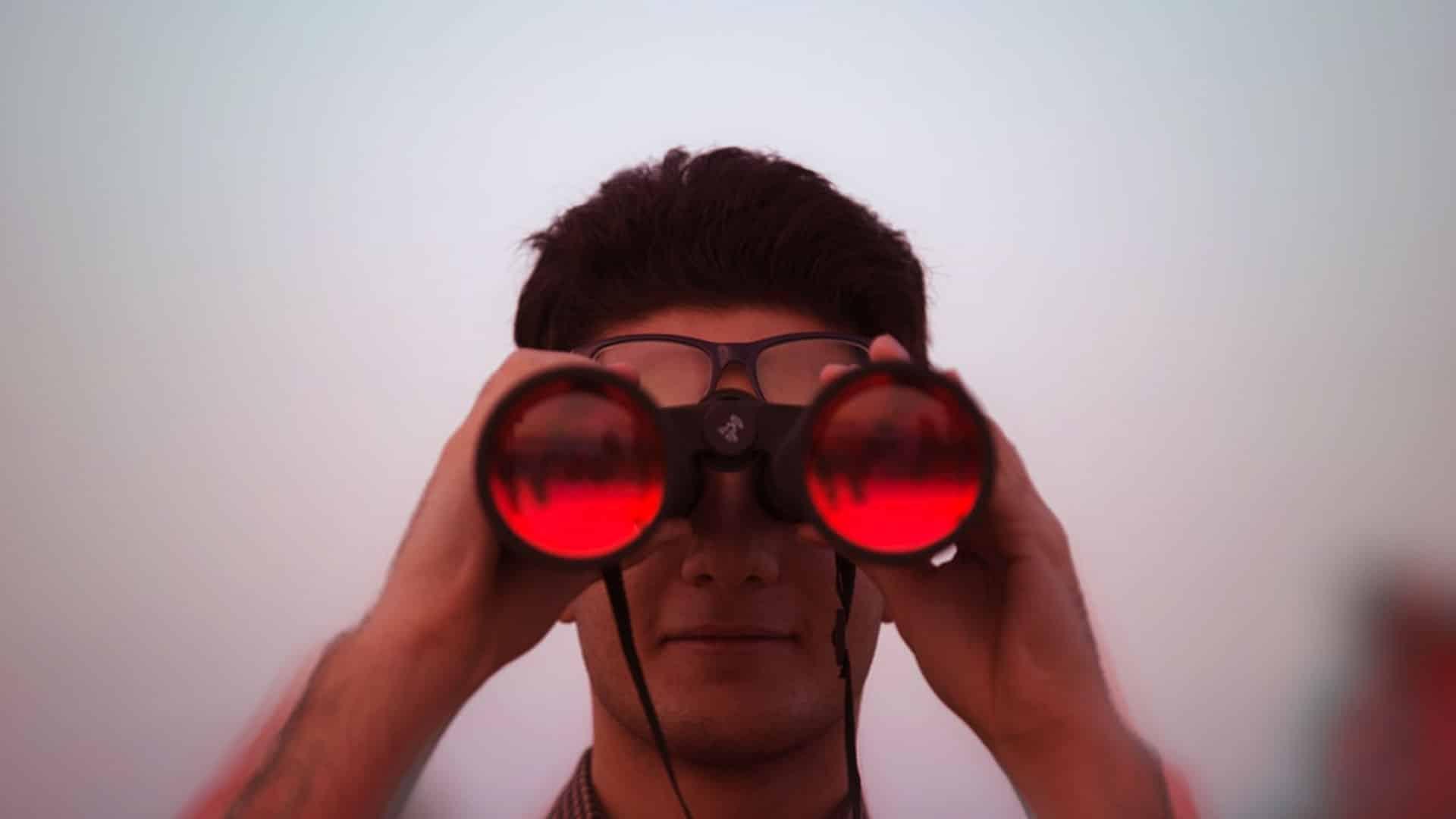 homme tenant dans ses mains des jumelles et regardant dans les jumelles de couleur rouge