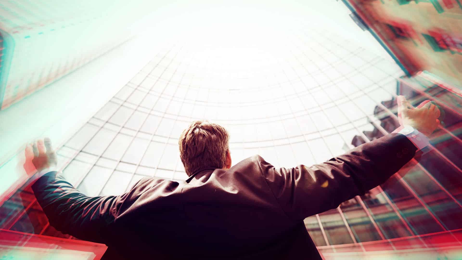 homme qui léve les bras vers le ciel regardant les buldings