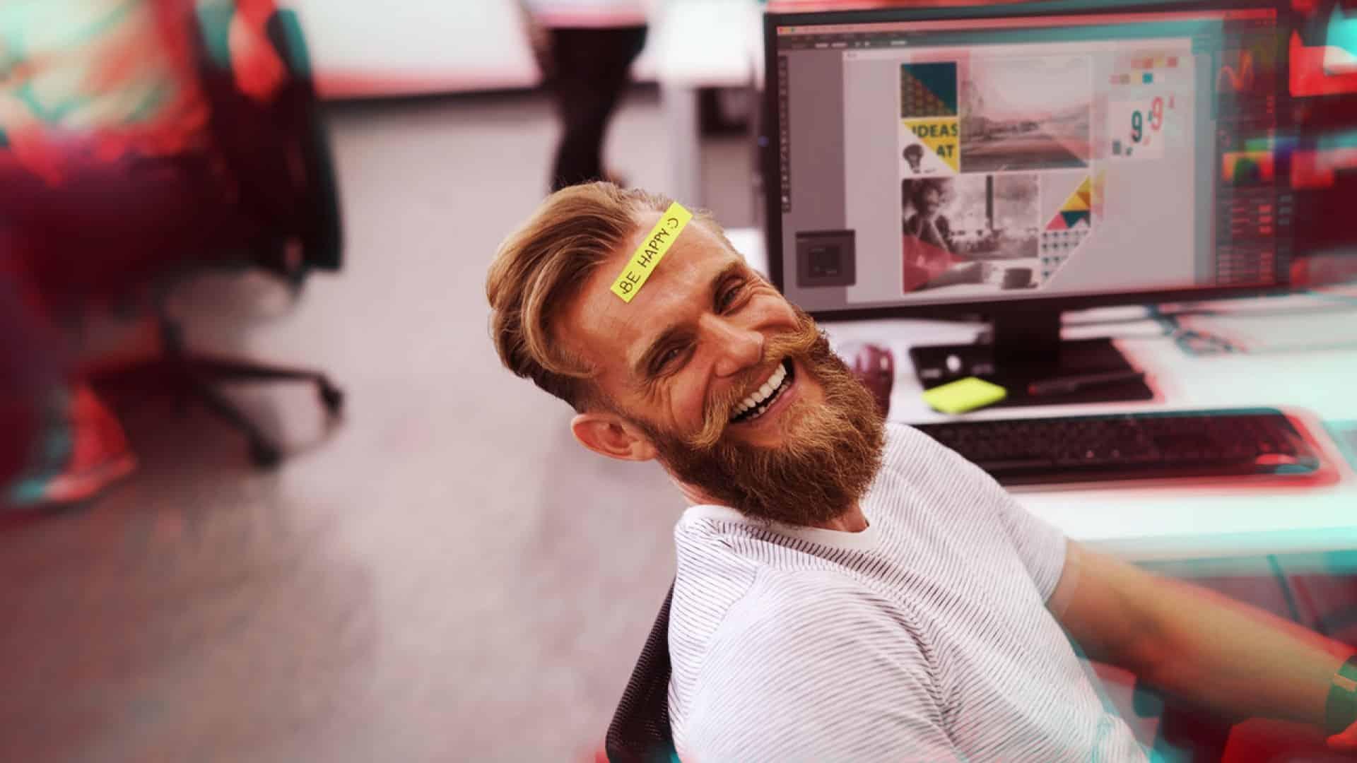 un homme avec une barbe et moustache assis dans des bureaux devant son ordinateur souris avec un post it sur le front