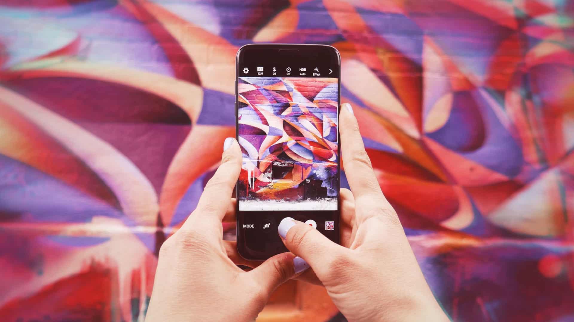 Personne prenant en photo un mur coloré et appuyant sur le bouton