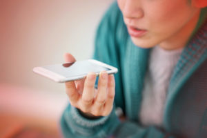 femme qui tient un téléphone dans sa main et qui parle au téléphone