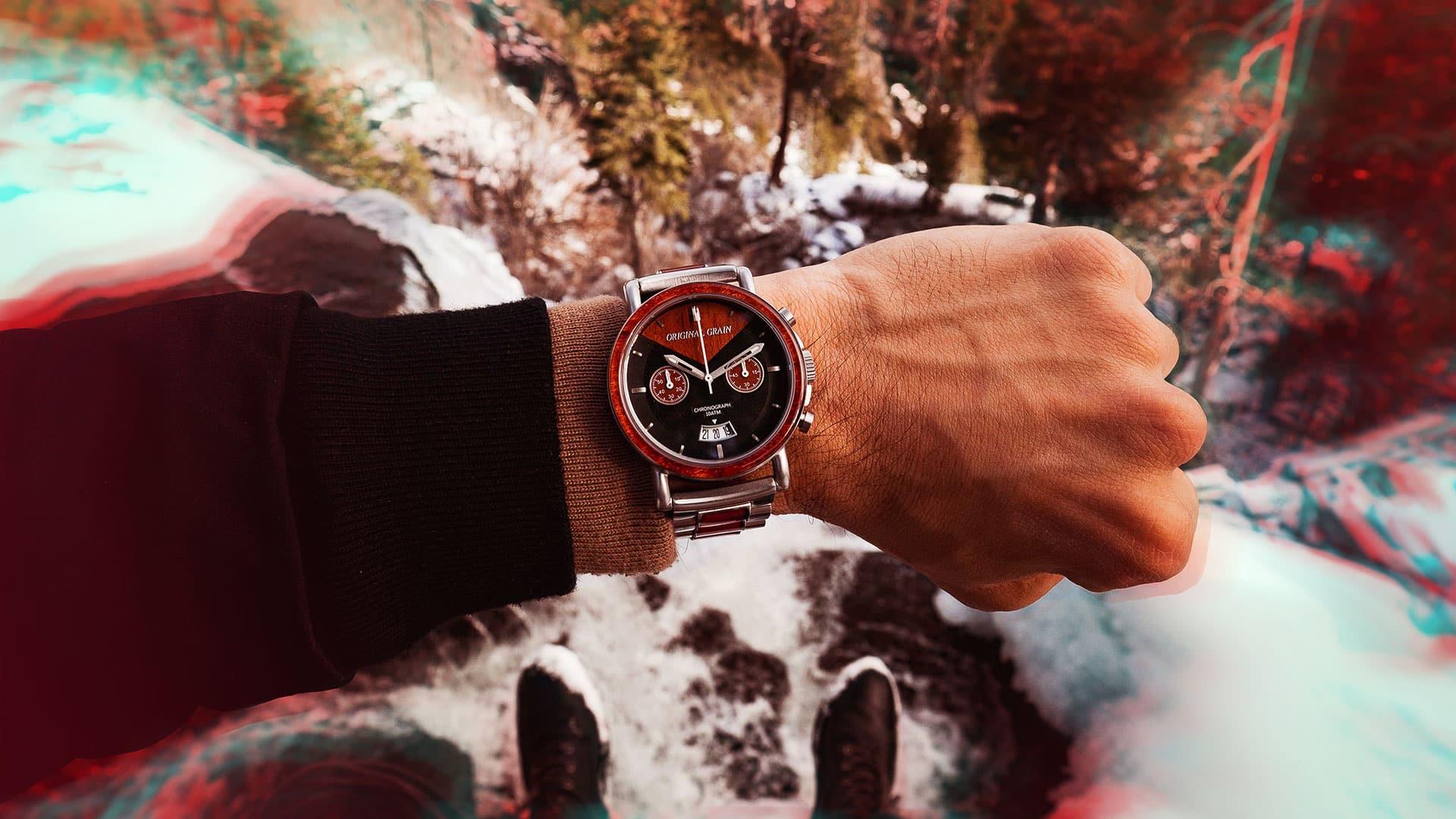 homme avec une montre au poignet avec de la neige a ses pied