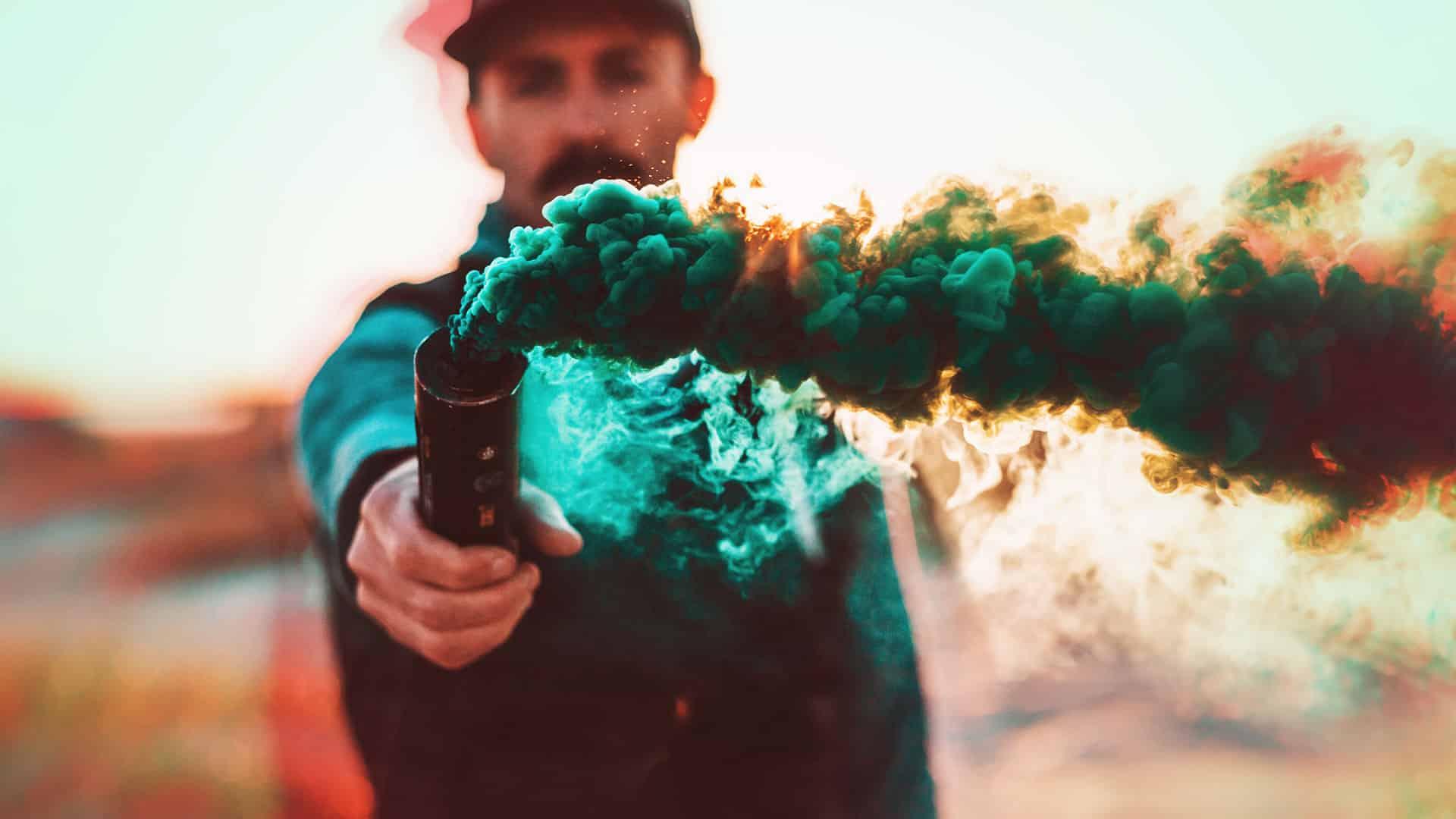 homme qui tient un fumigène dans la main avec de la fumée