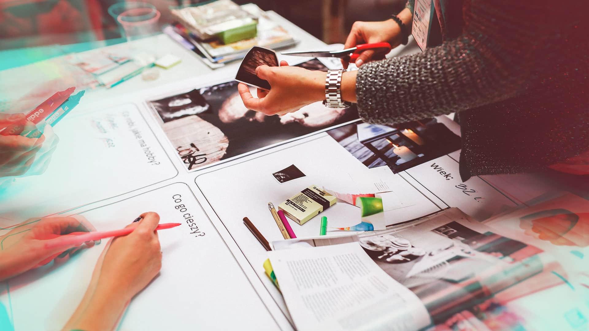personne dessinant et coupant des papiers sur une table avec crayon de couleur et magazine