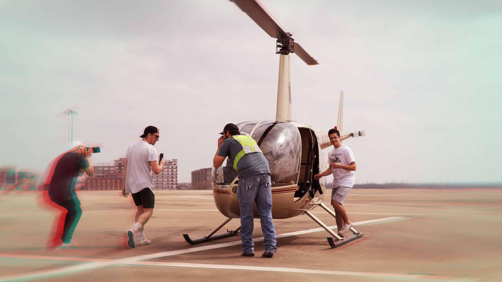 personne prenant en photo une personne devant un hélicoptère