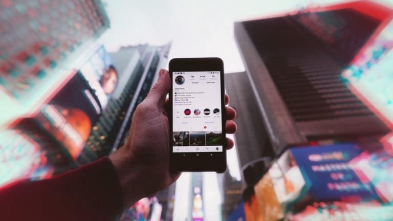 main qui tient un téléphone dans la rue