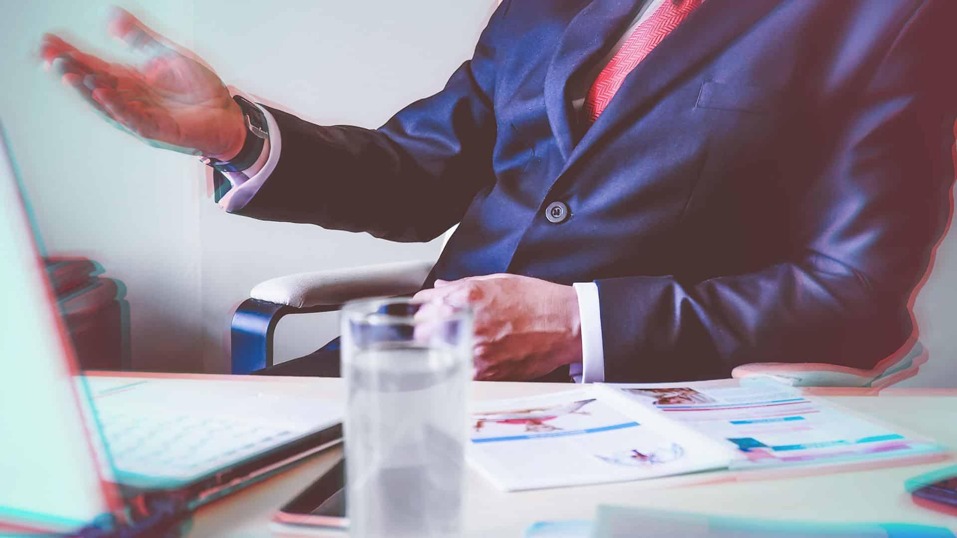 buste d'une personne assis sur un bureau levant la main gauche avec un verre et des feuilles sur le bureaux