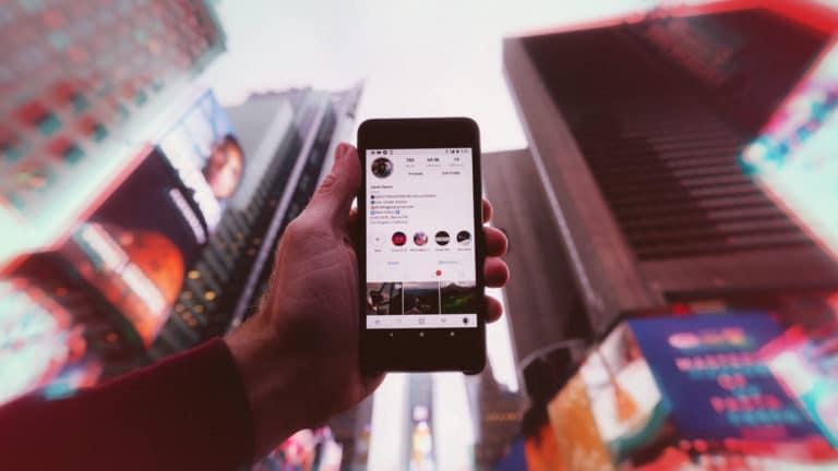 homme tenant son téléphone dans les mains avec comme écran d'accueil son profil instagram dans la rue au milieu d'immeubles