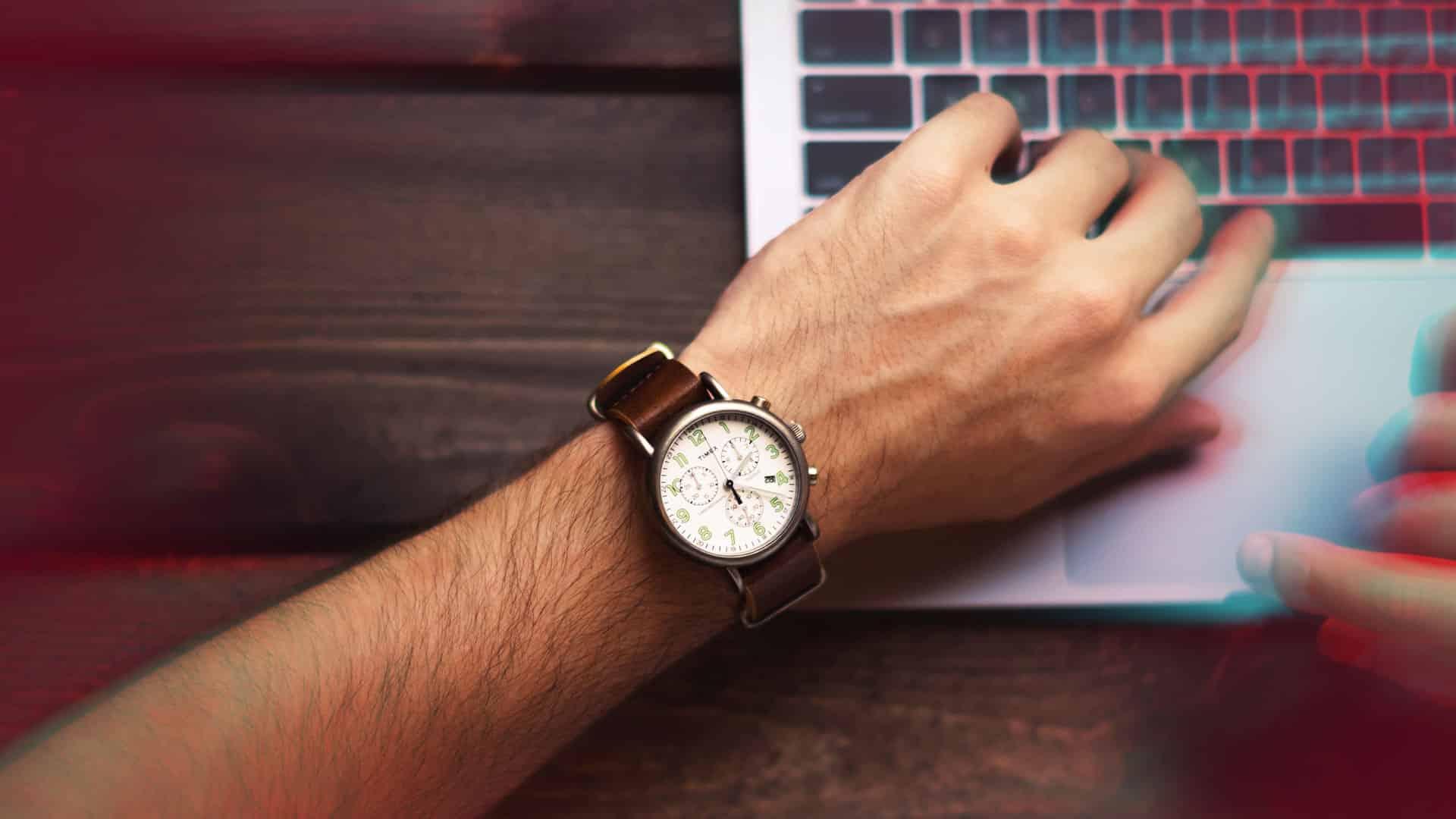 homme qui a la main sur son ordinateur sur un bureau avec une montre au poignet