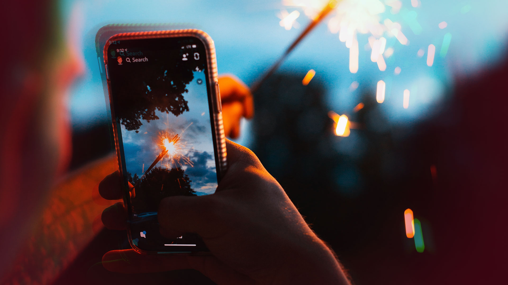 prendre une photo avec son téléphone avec un feu artifice dans l'écran