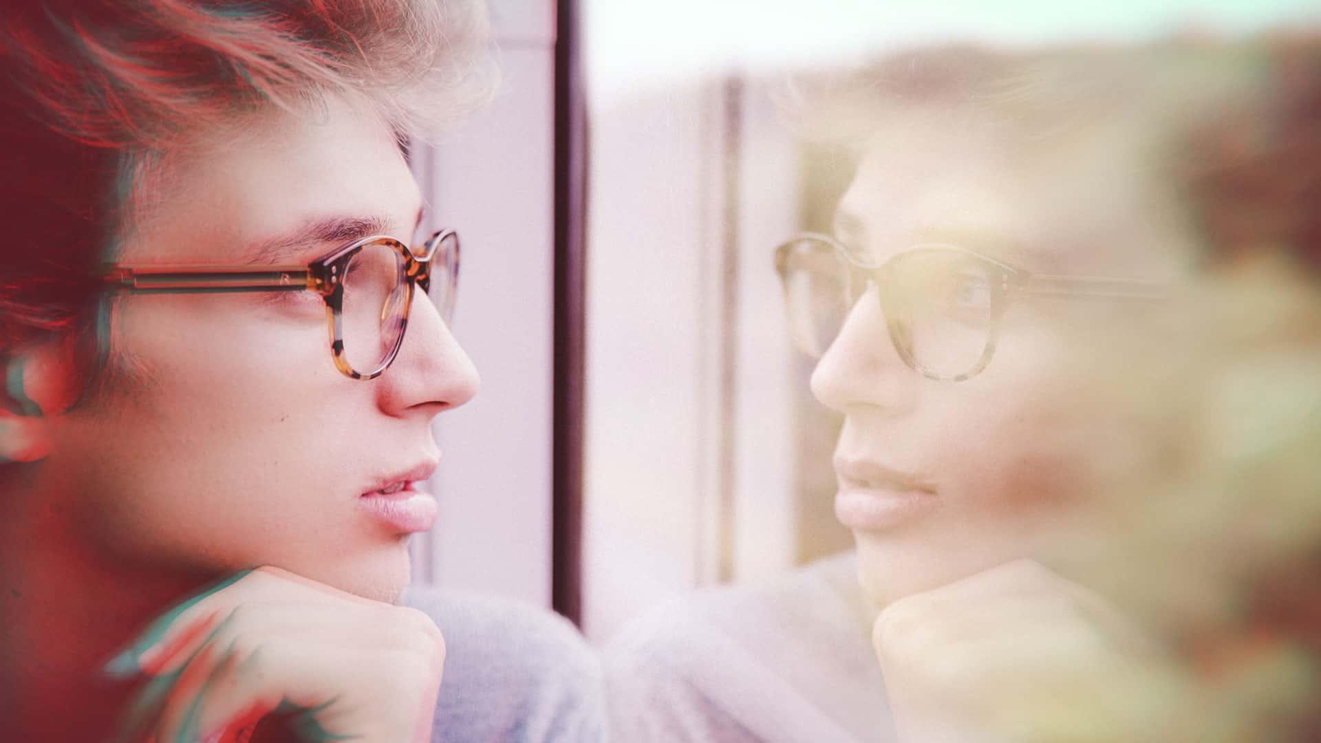 homme avec des lunette qui se regarde dans une vitre , on voit son reflet