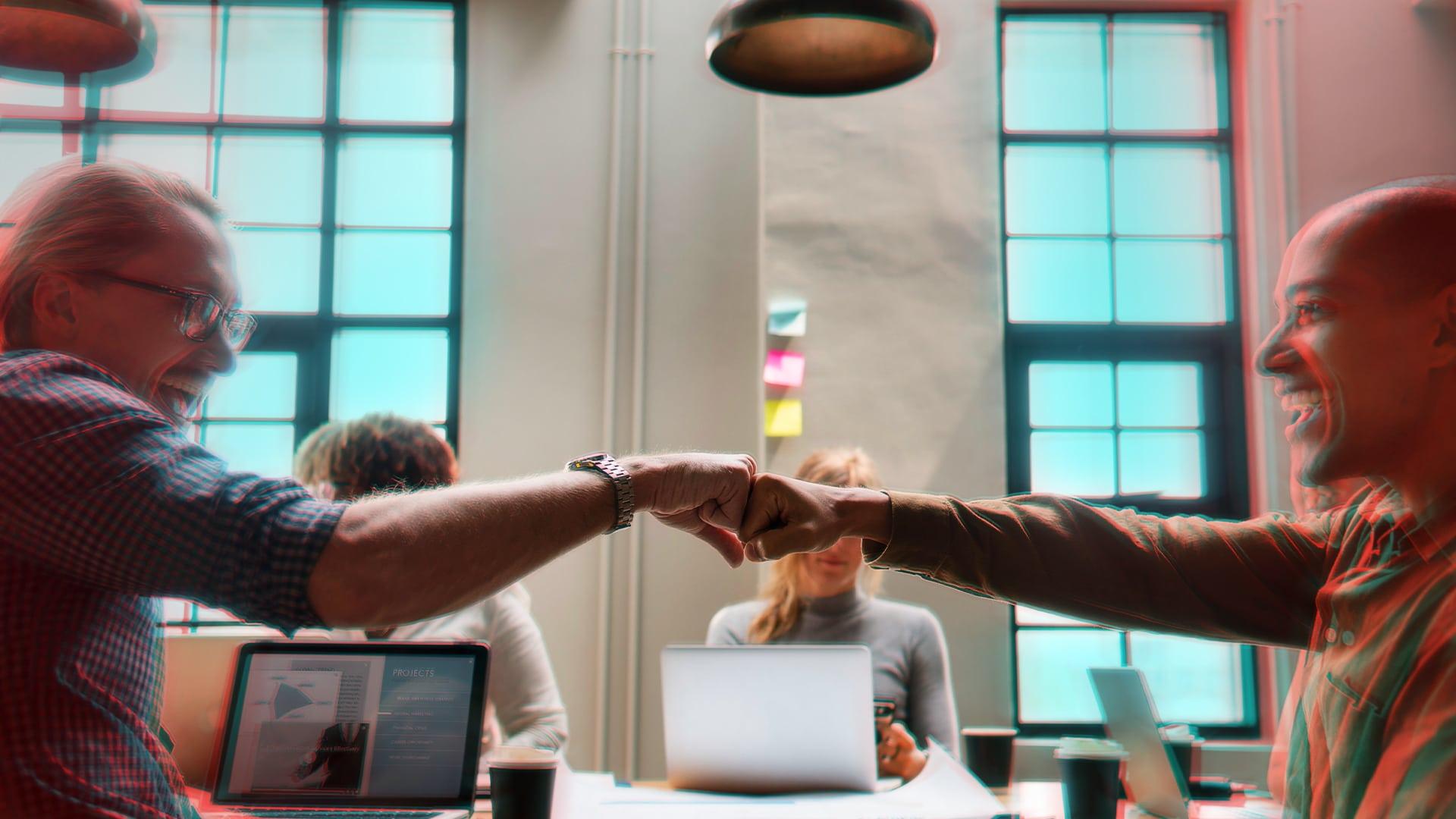 deux hommes dans un bureaux qui se tape les poings