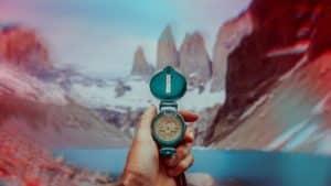 main qui tient une boussole devant un lac et des montagnes avec de la neige