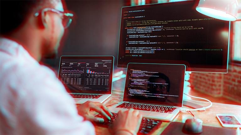 Homme qui a trois ordinateur devant lui et qui écrit des lignes de code informatiques